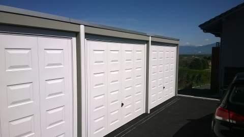 Trois garages préfabriqués en béton avec porte blanche à motif cassette