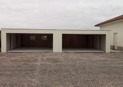 Face à unsix garages accolés communicants : vue de l'intérieur à travers les deux larges portes sectionnelles ouvertes