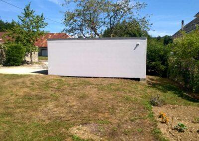 Vue latérale d'un garage simple, avec une sortie du tuyau d'évacuation des eaux de pluie en hauteur