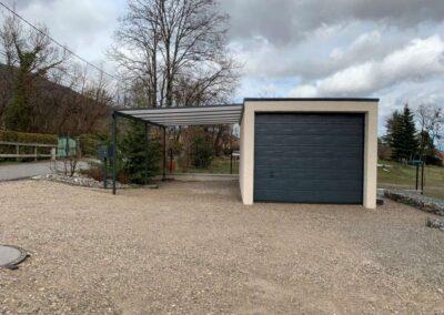 Un garage en béton simple, avec porte sombre et carport léger atenant