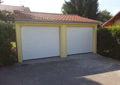Garage double préfabriqué en béton, crépis jaune, toiture en tuile