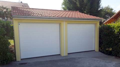 Garage double en béton préfabriqué, crépis jaune, portes blanches, toiture deux pans en tuiles