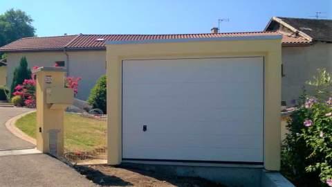 Garage en béton préfabriqué monobloc avec crépis jaune et porte sectionnelle blanche