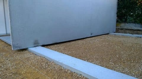 Garage posé sur deux poutres en béton
