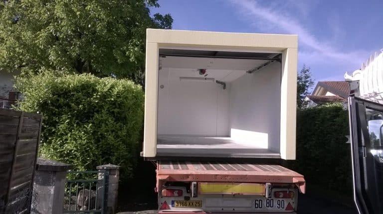 Garage simple avec crépis ocre et porte sectionnelle blanche