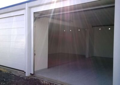 Intérieur d'un garage double communicant, depuis l'extérieur via une porte ouverte