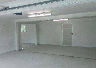 Intérieur d'un garage communicant : deux néons, interrupteur, motorisation de porte, fenêtre