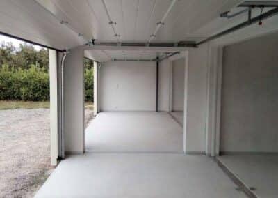 Intérieur d'un garage composé de six blocs, vue de l'ensemble traversant de deux blocs