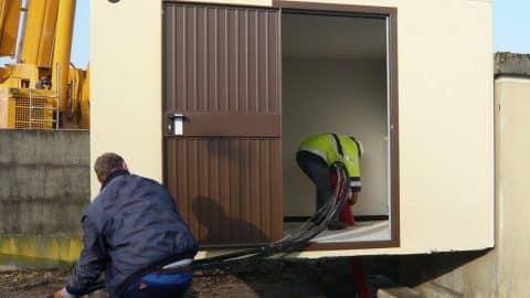 Techniciens passent des câbles dans la dalle du local