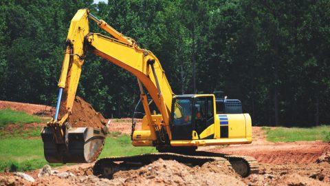 Pelleteuse jaune creusant la terre