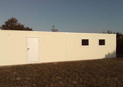 Façade d'un garage en béton monobloc double, traversant dans la longueur. Avec uneporte de service blanche et deux fenêtres