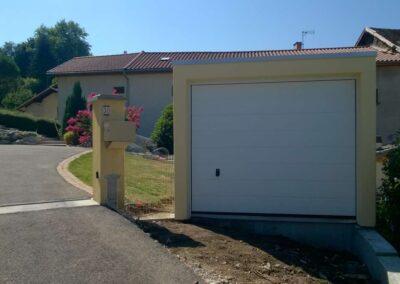 Garage simple en béton, crépis coloris jaune, porte blanche sectionnelle