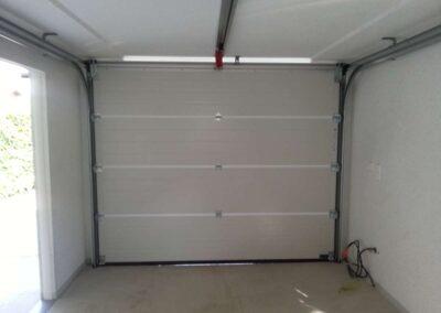 Porte sectionnelle blanche à nervures verticales, manuelle, vue depuis l'intérieur d'un garage