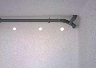 Tuyaux en pvc gris à l'intérieur et grilles de ventilation dans un garage