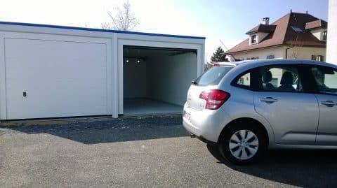 Voiture stationnée devant un garage double préfabriqué en béton